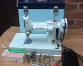 White Vintage Singer 221, 221K Portable Featherweight Sewing Machine with attachments.