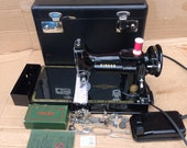 Vintage Singer 221K Featherweight Sewing Machine with attachments and instruction manual.