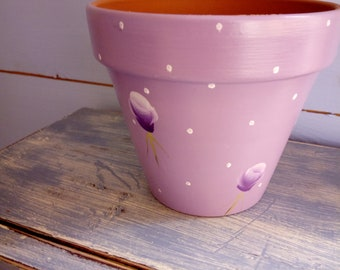 This is a handpainted plant pot in a lavender colour with purlpe handpainted flowers and white polka dots