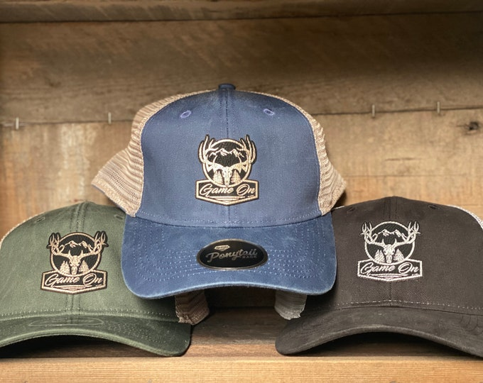 Game On ponytail hat-unstructured with hook and loop enclosure. Opening to pull ponytail through.