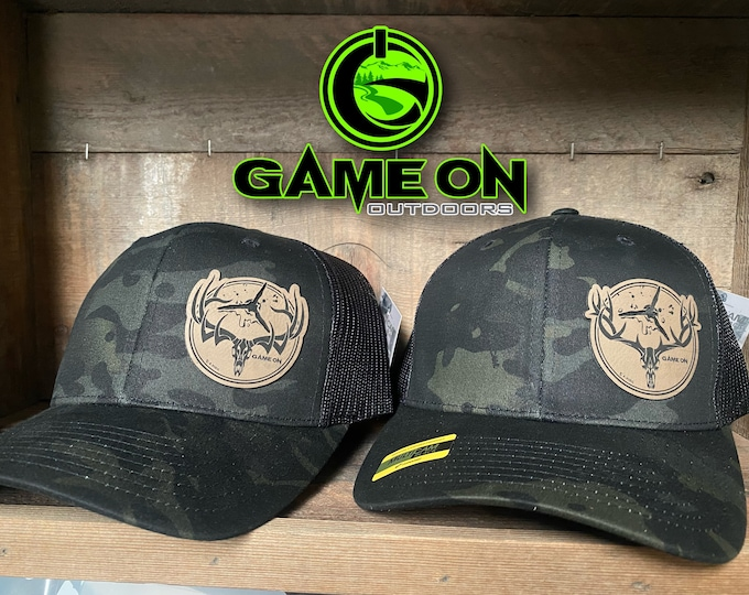 GAMEONGAMEOVER buck and bull SnapBack hat with a broad head puncture patch.