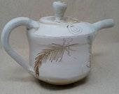Small white teapot with metallic surface designs