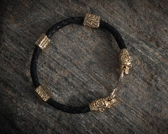 Bronze viking bracelet with bear heads on black leather. torc. Ethnic style. Decorated with runes teiwaz, Ingus, Soulu. Totem, amulet.