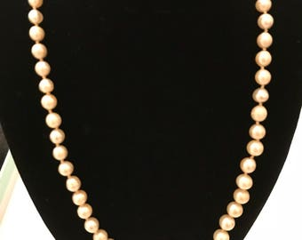 Vintage long strand of faux pearls with silver clasp .