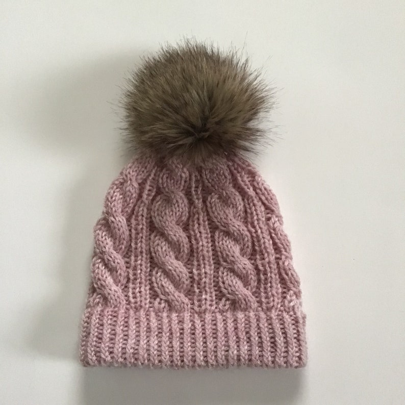 6fb2e7b6c6b Hand knitted blush pink cable beanie with faux fur pom pom