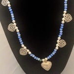 Hearts in abundance!  Lovely beaded necklace with filigree hearts and blue glass cats eye beads.