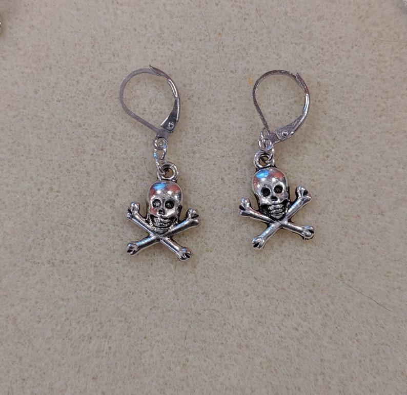 Spooky earrings. Skull and crossbones silver dangles. image 0