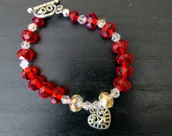 Fit for a Queen.  A Red Queen, that is.  A silver filigree heart is the focus of this red and clear glass bead 6 inch bracelet.