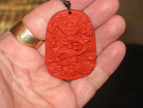 Hand carved red organic cinnabar Dragon pendant.