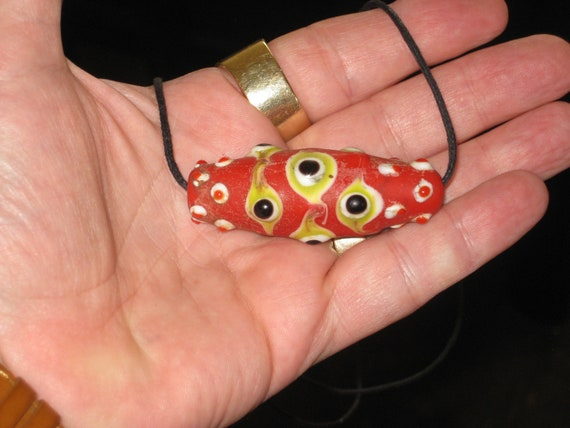 Hand made glazed organic cinnibar pendant with 29 eyes.