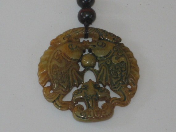 All natural hand carved two sided Jade fish pendant, with adjustable necklace.