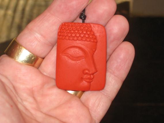 Hand carved red organic cinnabar Buddha pendant.