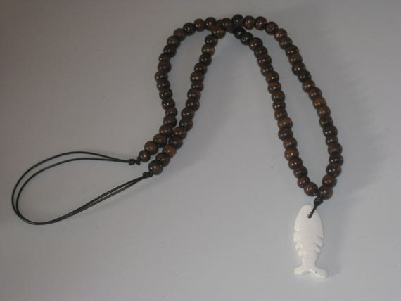 Hand carved buffalo bone pendant and wood beads from Africa.