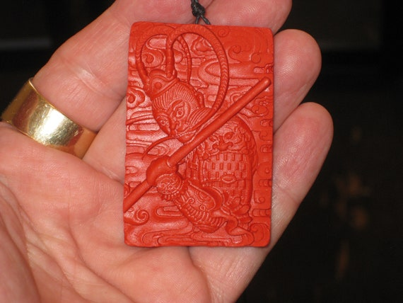 Hand carved red organic cinnabar warrior pendant.