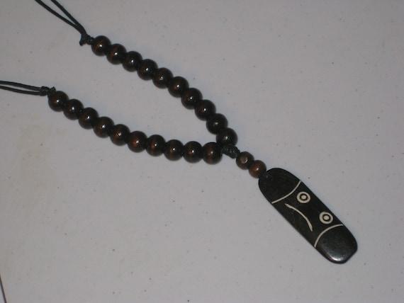 Buffalo bone pendant and wood beads, with adjustable necklace.