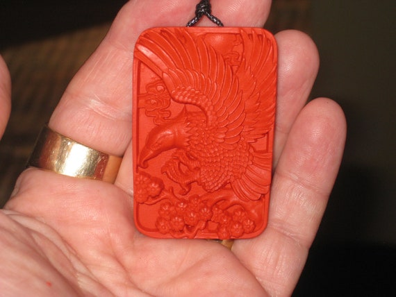 Hand carved red organic cinnabar eagle pendant.