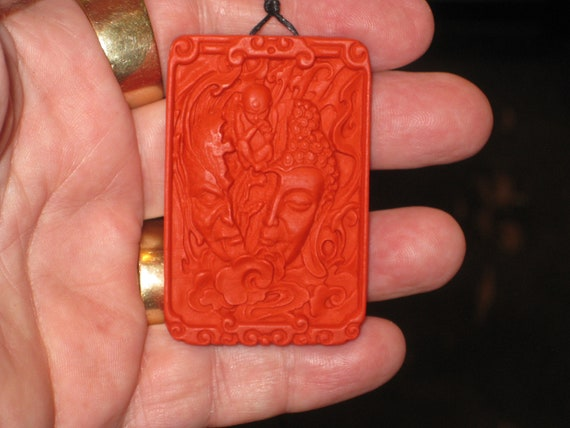 Hand carved red organic cinnabar Buddha and devil head pendant.