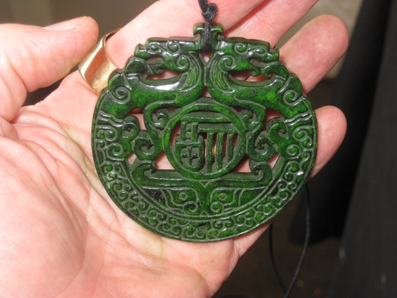 All natural jade hand carved two sided dragon pendant, with adjustable necklace.