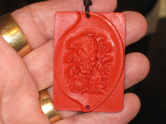 Hand carved red organic cinnabar devil pendant.