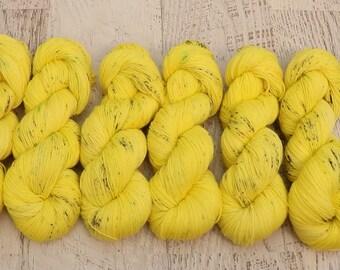 Yellow Speckled Fingering Weight Sock Yarn (75/25 Superwash Merino/Nylon) handdyed in bright yellow w/ black, green, &orange speckles 100g