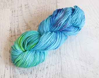 Kettle Dyed Worsted Weight Cotton Yarn (100% Cotton) hand dyed in multiple hues of blue, yellow, teal, with some pink speckles
