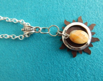 Bronze sunburst with silver encircled stone pendant.