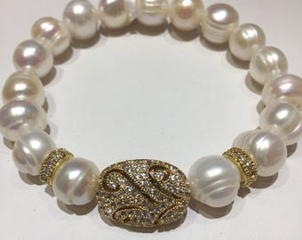 Fresh water pearls beaded stretch braclet with a gold plated bead bedazzled with zirconia.