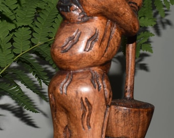 Hand carved woman with child pounding rice