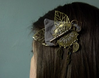 """Clamp """"La Clef d'Alice"""" ellegable hairdressing accessory with gray petals and bronze leaves surmounted by a retro steampunk bronze key"""