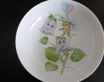 Hand painted porcelain soup plate from birth. Pattern of two purple flowers and a bee holding two balloons