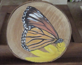 Butterfly painted on wood with bark on yellow flower pad