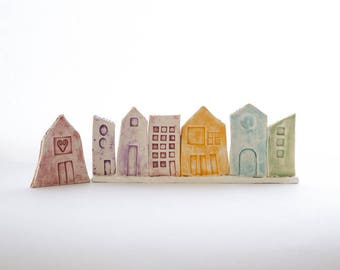 A rainbow of little houses ceramic naïve and amazing shapes, enameled in cheerful colors, purple, green, orange