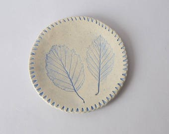 Ceramic blue enamel cup with imprints of leaves