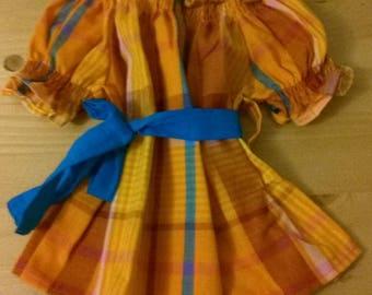 girl in madras sleeved smocked dress