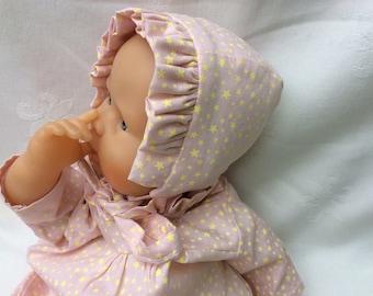 Pink fabric bonnet has neon star doll 30 cm