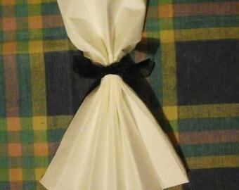 Plain white dress napkin folding and a black ribbon