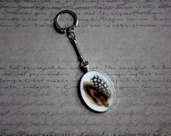 Oval key in metal, resin and 2 feathers