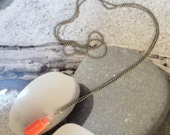 Necklace and her vial of neon orange