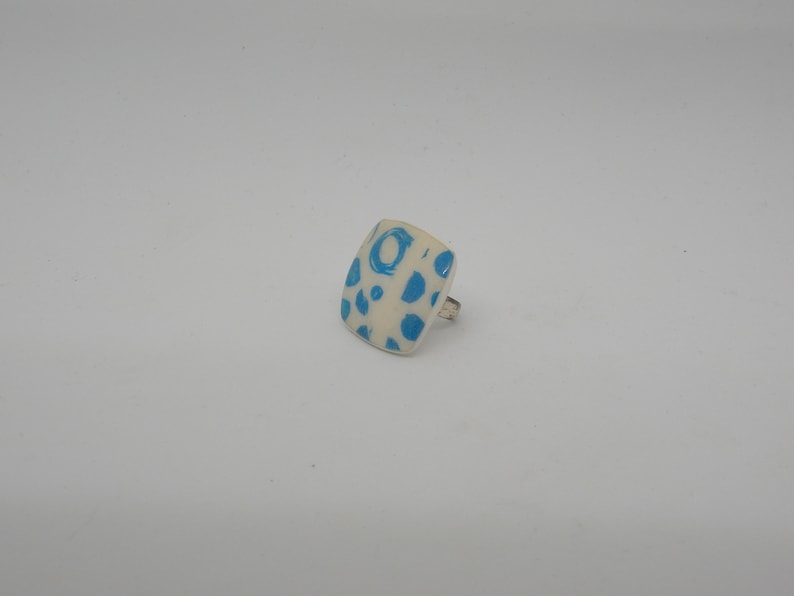 Square ring in white and round blue polymer paste