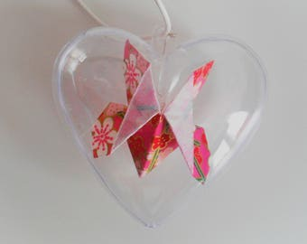 Pink butterfly origami in a heart of plastic decoration