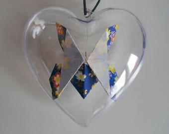 Blue butterfly origami in a heart of plastic decoration