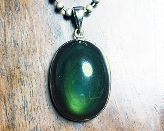 Pendant, obsidian eye celeste ,from Mexico, of high quality. 925 silver crimping. Dimensions 42/23/16mm. Natural obsidian.