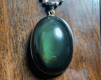 Pendant, obsidian eye celeste ,from Mexico, of high quality. 925 silver crimping. Dimensions 52/30/17mm. Natural obsidian.