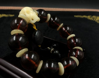 large carved skull bracelet, Burmese red amber, obsidian eye yack bone celeste 18mm beads.