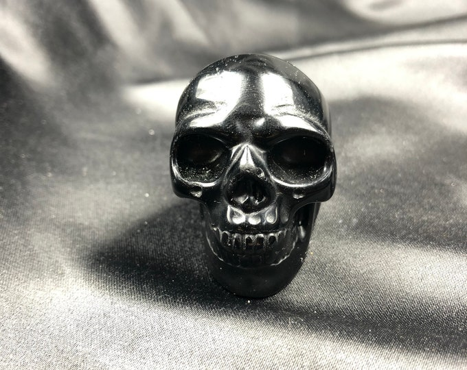 Crystal skull. Skull carved with black obsidian hand. 5cm in length.