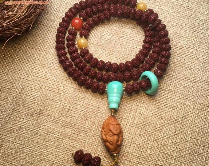 Mala, chapelet bouddhiste, 108 perles de Rudraksha, turquoise, agate nan hong, jade néphrite. Ganesh sculpté à main dans un noyau d'olive.