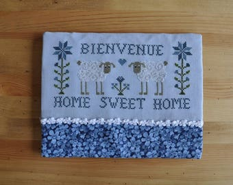 embroidered blue 'welcome' cross stitch frame