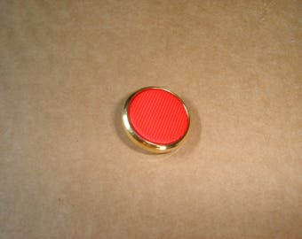 a vintage gold and red tail button