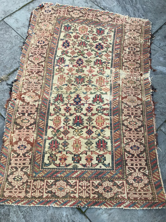 Caucasian fragment/rug. Collector's piece. Kufesque border. All over pattern  in field, worn, w/ holes. Hand knotted vegetable dyed wool