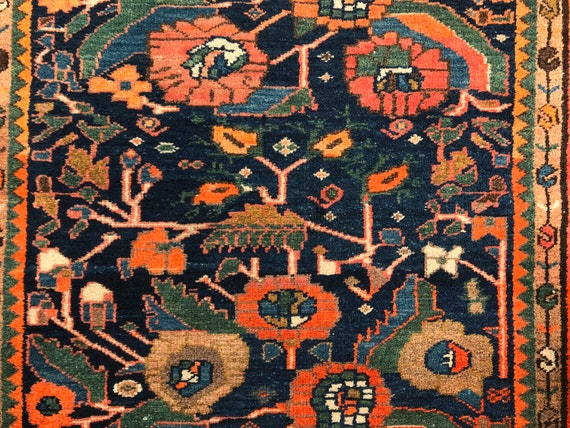 SOLD. Antique village rug. Hand knotted wool. Organic dyes, blue, orange,green, stylized flower head and leaf motifs